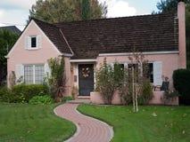 桃红色房子和砖足迹 免版税库存图片