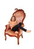 桃红色扶手椅子的女孩 库存图片