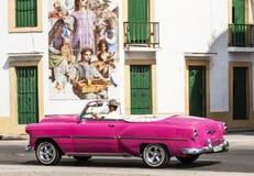 桃红色敞篷车通过的壁画在哈瓦那古巴 库存照片