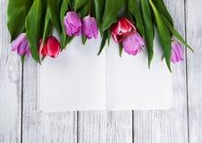 桃红色新鲜的郁金香和笔记本 免版税库存照片
