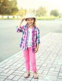 戴桃红色方格的衬衣和帽子的美丽的微笑的小女孩孩子 免版税库存照片