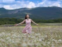 桃红色无袖的礼服的女孩在春黄菊草甸走  库存照片