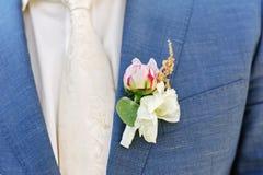 桃红色日工钮扣眼上插的花被别住对新郎夹克 库存图片