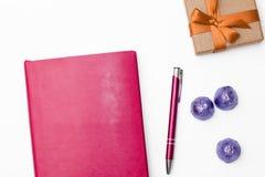 桃红色日志、笔、一些巧克力在一个蓝色封皮和礼物盒在白色背景 库存照片