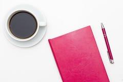 桃红色日志、笔和一杯在白色的无奶咖啡 免版税图库摄影