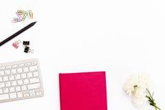 桃红色日志和键盘在白色背景 最小的女性企业概念 图库摄影