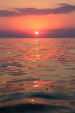 桃红色日落的反射在海 库存照片