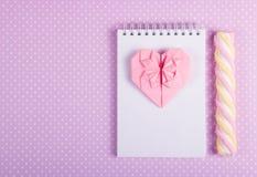桃红色有一张空白页和棍子蛋白软糖的华伦泰origami开放笔记本在圆点背景  库存图片