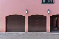 桃红色有两辆汽车车库的色的房子 库存照片