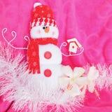 桃红色有白色木槿花和白色闪亮金属片的背景圣诞节红色雪白雪人软的玩具 图库摄影