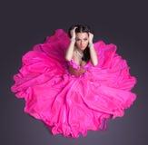 桃红色服装的俏丽的舞蹈演员坐楼层 库存图片