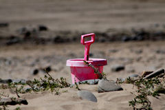 桃红色桶和小铲在海滩 库存图片