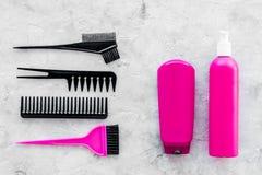 桃红色梳子、刷子和浪花美发师的研究石书桌背景顶视图 免版税库存照片