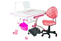 桃红色椅子、桃红色学校书桌、桃红色篮子、台灯和黑支持在腿下 免版税图库摄影