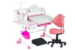 桃红色椅子、桃红色学校书桌、桃红色篮子、台灯和黑支持在腿下 库存照片