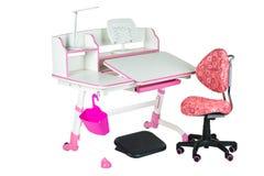 桃红色椅子、桃红色学校书桌、桃红色篮子、台灯和黑支持在腿下 库存图片
