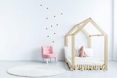 桃红色椅子对有贴纸的白色墙壁在简单的孩子` s bedr 库存图片