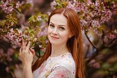 桃红色樱花背景的红发女孩在sprin的 免版税库存图片