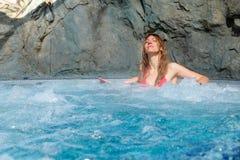 桃红色比基尼泳装的俏丽的妇女在一个浴盆放松 库存照片