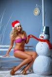 桃红色比基尼泳装的女孩有雪人的 免版税库存照片