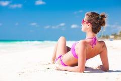桃红色比基尼泳装的妇女在热带海滩 免版税库存照片