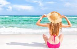 桃红色比基尼泳装的妇女在白色海滩 图库摄影