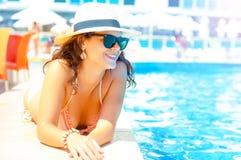 桃红色比基尼泳装的性感的妇女享受日落的 免版税库存照片