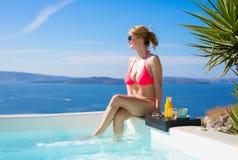 桃红色比基尼泳装的晒日光浴的妇女 免版税库存图片