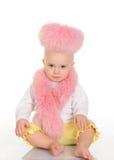 桃红色毛皮的逗人喜爱的婴孩坐空白背景 免版税库存照片