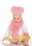 桃红色毛皮的逗人喜爱的婴孩坐空白背景 图库摄影