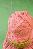 桃红色毛线和编织针一个球在一块全国板材 免版税图库摄影