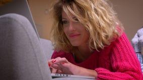 桃红色毛线衣的特写镜头白肤金发的主妇说谎在胃微笑地观看入膝上型计算机的在舒适家庭环境 股票视频