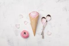 桃红色毛茛属花冰淇凌在奶蛋烘饼锥体的在舱内甲板的白色台式视图放置称呼 美好的创造性的花卉题材 图库摄影
