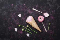 桃红色毛茛属花冰淇凌在奶蛋烘饼锥体的在舱内甲板的黑台式视图放置样式 美好和创造性的花卉题材 免版税图库摄影