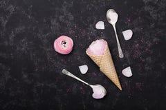 桃红色毛茛属花冰淇凌在奶蛋烘饼锥体的在舱内甲板的黑台式视图放置称呼 美好的创造性的花卉题材 库存照片