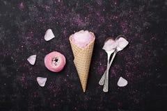 桃红色毛茛属花冰淇凌在奶蛋烘饼锥体的在黑在舱内甲板的桌顶上的视图放置称呼 美好的花卉题材 免版税库存图片