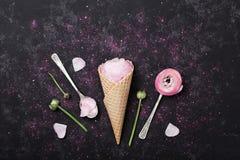 桃红色毛茛属花冰淇凌在奶蛋烘饼锥体的在黑桌上在舱内甲板从上面放置称呼 美好的创造性的花卉题材 免版税库存照片