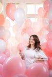 桃红色气球的美丽的女孩 免版税库存照片