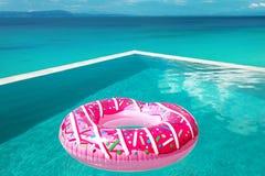桃红色水池浮游物 在无限游泳池的大可膨胀的多福饼 库存照片