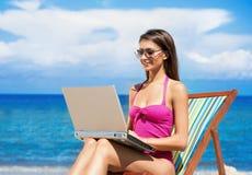 桃红色泳装的一个少妇有在海滩的一台计算机的 免版税库存照片