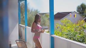 桃红色泳装的女孩完成她的饮料并且从阳台出去 股票录像