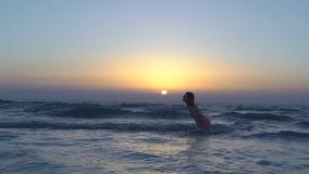 桃红色泳装的美丽的妇女在海滩跑晒黑,海上或海洋坐 对日落的愉快的女孩奔跑 股票视频