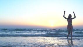 桃红色泳装的美丽的妇女在海滩跑晒黑,海上或海洋坐 对日落的愉快的女孩奔跑 影视素材