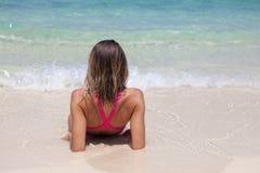 桃红色泳装的美女在白色沙滩说谎 库存照片