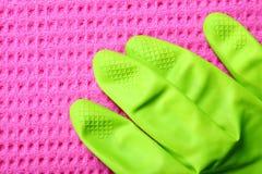 桃红色海绵和绿色橡胶手套 免版税图库摄影