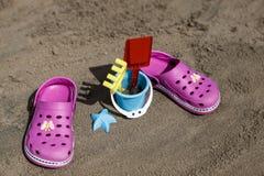 桃红色海滩crocs和蓝色沙子在沙滩戏弄 在前景和被弄脏的海使触发器靠岸在背景中 图库摄影