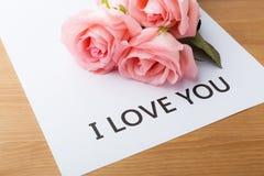 桃红色消息玫瑰和礼品券我爱你 免版税库存图片