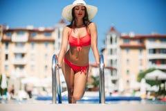 桃红色游泳衣的一个美丽的女孩晒日光浴由游泳池的 晴朗的天气 夏天 图库摄影