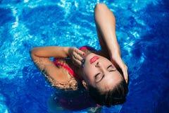 桃红色游泳衣的一个美丽的女孩晒日光浴由水池的 晴朗的天气 夏天 免版税库存图片