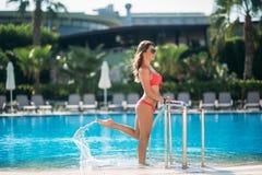 桃红色游泳衣的性感的女孩晒日光浴由游泳池的 晴朗的天气 免版税图库摄影
